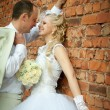 Stock Photo: Bride and groom near the wall