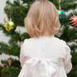 Adorable little girl decorating a Christmas tree — Stockfoto