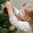 Smiling little girl decorating a Christmas tree — Stock Photo