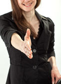 Young smiling businesswoman reaching out hand for handshake — Stock Photo