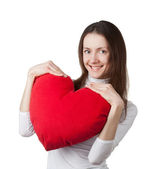 Attractive smiling brunette girl holding big red heart — Stock Photo
