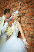 Bride and groom near the wall — Stock Photo