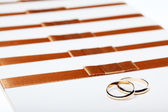 Ivory wedding invitations with rings — Stock Photo