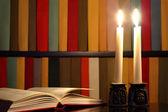 Opened book, candles and bookshelves in the background — Stock Photo