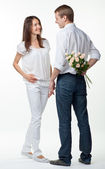 Romantic date: guy presenting flowers to young lady — Stock Photo