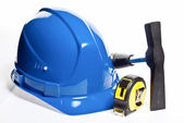 Hammer, tape line and blue hardhat — Stock Photo