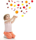 Little girl reaching her hands out and catching fruits — Stockfoto