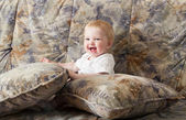 Happy baby girl sitting on a sofa — Стоковое фото