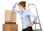 Sad young woman near a pile of boxes — Stock Photo