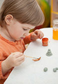 Beautiful little girl cover with drawings clay toys — Stock Photo