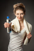 Young woman with bottle of water after fitness exercise — Stock Photo