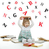 Scared little girl sitting surrounded by books and alphabetical — Stock Photo