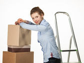 Smiling young woman near a pile of boxes — Stock Photo