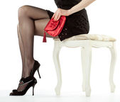 Beautiful legs of young woman sitting on a banquette holding red — Stock Photo