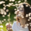 Young woman holding dandelion — Stock Photo