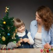 Happy smiling baby girl and her mummy decorate the Christmas tree — Stock Photo