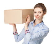 Smiling young woman carrying a big box — Stock Photo