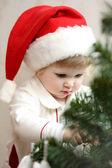 Baby girl decorate the Christmas tree — Stok fotoğraf