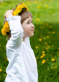 Little girl trying on yellow chaplet made of dandelions — Stock Photo