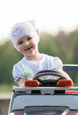 Smiling little girl steers electromobile — Stock Photo