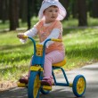 Beautiful baby girl rides tricycle  — Stock Photo