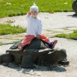 Baby sitting on a stone turtle — Stock Photo #22619441