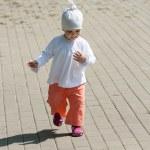 Baby girl walking on the street — Stock Photo #22619515