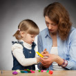 Young mother and her daughter modelling with plasticine, dark background — Stock Photo