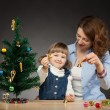 Happy smiling baby girl and her mummy decorates the Christmas tree — Stock Photo #22619591