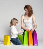 Menina com a mãe dela olhando para dentro de sacos de compras — Foto Stock