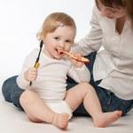 Beautiful baby girl cleaning her teeth — Stock Photo