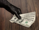 Human hand in black glove holding dollars — Stock Photo