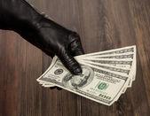 Human hand in black glove holding dollars — Stock Photo