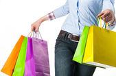 Bolsas de papel multicolores en mano femenina — Foto de Stock