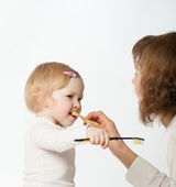 Young mother helping her little dauther cleaning her teeth — Stock Photo