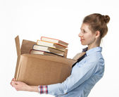 Smiling woman carrying a box with books — Stock Photo