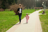 Running young mother and her daughter in a spring park — Stock Photo