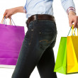 Woman holding multicolored shopping paper bags — Stock Photo