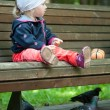 Little girl sitting on a bench and feeding pigeons — Stock Photo #24685851