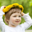 Little girl trying on yellow chaplet made of dandelions - Stock Photo