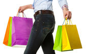 Woman holding multicolored shopping paper bags — Photo