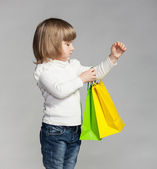 Little girl holding multicolored shopping bags — Stock Photo