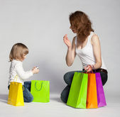 Little girl with her mother examining purchases — Stock Photo