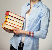 Girl holding a stack of books — Stockfoto