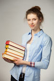 Smiling girl holding a stack of books — Stock Photo