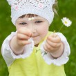 Beautiful little girl holding camomiles - Stock Photo