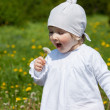 Little girl blowing on a white dandelion - Stock Photo
