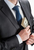 Businessman putting money in his pocket — Stock Photo