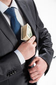 Businessman putting money in his pocket — Stockfoto