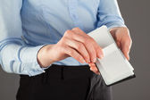 Businesswoman taking business card out of a holder — Stock Photo